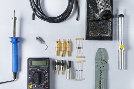 rca: Top view of Tools for home electrical repair - soldering iron, cable, solder, tin, soldering iron stand, resistor, Jack 3.5, xlr, rca, diode, pliers, scissors, cable stripper, multimeter. Flat lay