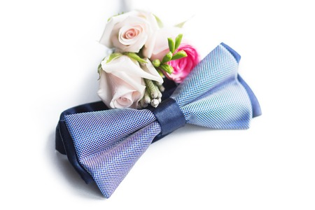 bridegrooms: blue plaid bow tie lies next to the grooms boutonniere isolated on a white background. Wedding concept. bridegrooms pastel accessories such as bow-tie and flowers on the marriage day.
