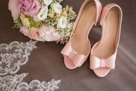 Stylish fashion pink high heels with a bow on the background room, glamor, bridal, wedding 免版税图像