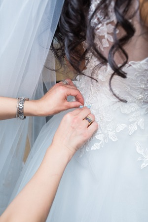 bridesmaid: bridesmaid tying bow on white wedding dress