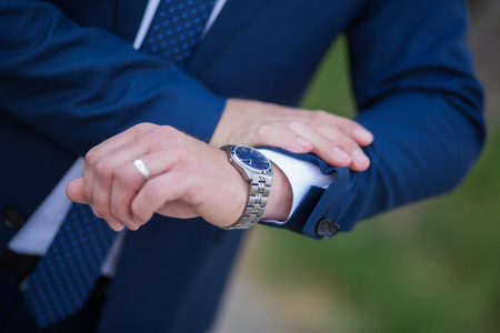 french cuffs: The man in the white shirt and blue tie wears watches.