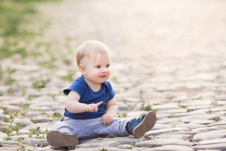 Happy cute boy on old roadway. Smiling one child outdoors on Road paved with stone on the sunset Stock Photo
