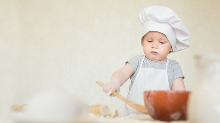 a little dinner: Portrait of the little boy in a suit of the cook sculpts dough. Baby make dinner in chef suit. Cooking concept with free text space - copy space