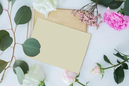 Draufsicht auf Hochzeit Hintergrund mit Karte. Mock-up für Text mit freiem Platz. Vorlage Einladung, weiß und rosa Rosen und Papier Papyrus. Falt legen Standard-Bild