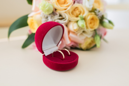 Two wedding rings in red box and spring blossoms. Wedding concept.