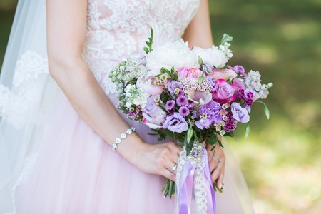 Beautiful wedding colorful bouquet with different flowers in the hands of the bride. Bridal summer bouquet