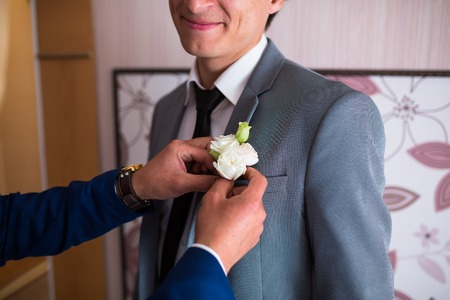 buttonhole: Friend of the bridegroom in a suit holding grooms buttonhole. Wedding boutonniere