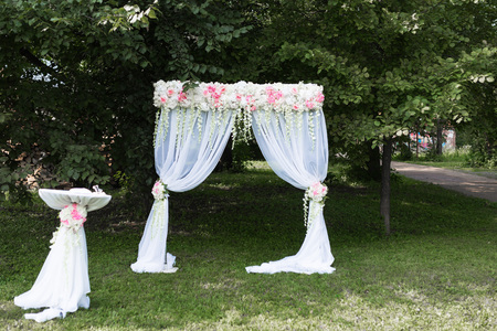Beautiful white arch with flower decorations for the wedding ceremony with chairs for guests on the green background with trees