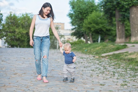 beautiful mother is walking on the old road with her little baby boy with first steps. One years old baby walking whith his mom outdoor