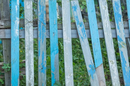 old fence: Shabby blue vintage wood background. Broken old fence with grass Stock Photo