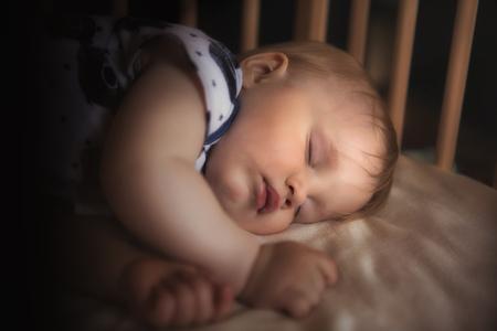 밤에 방에 그의 침대에서 자 고하는 평화로운 사랑스러운 아기. 소프트 포커스입니다. 잠자는 아기 개념. 집에서 1 살짜리 애무자는 잠을 자고, 램프에