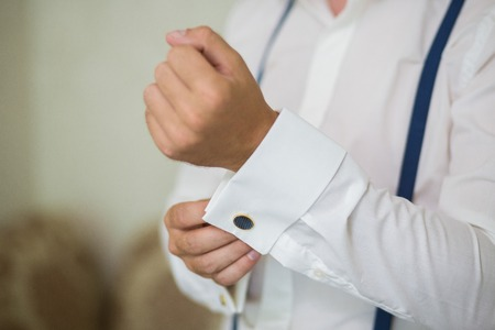 cufflink: close up of a hand man how wears white shirt with blue suspender and cufflink