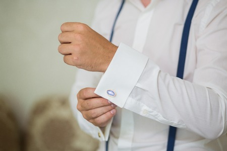 close up of a hand man how wears white shirt with blue suspender and cufflink