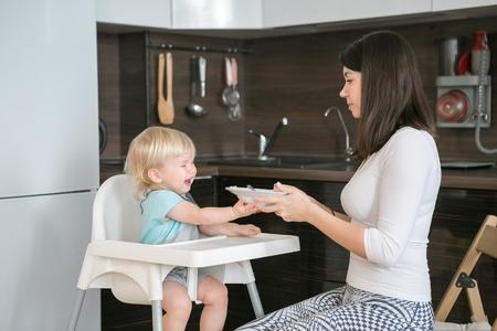 小さな男の子を食べることを拒否、彼は叫び、プレートをプッシュします。母は彼女の子供を供給します。歳の子供のための最初の固形食。赤ん坊 写真素材