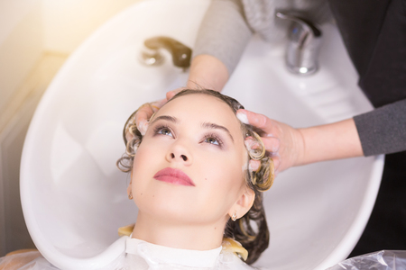 hairstylists: Washing hair procedure. Client is resting while her hair is being cleansed by hairstylist.
