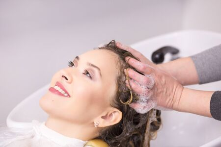 Portrait of young women which wash hair in a beauty salon after hair coloring Stock Photo