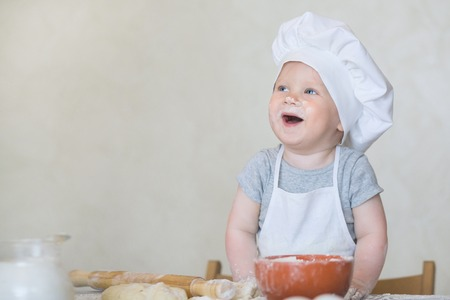 Prodigy: The little baby boy in a suit of the cook sculpts dough. Small kid scullion make dinner in chef suit. Cooking child lifestyle concept. Toddler enjoy, having fun, learning and playing in the kitchen Zdjęcie Seryjne