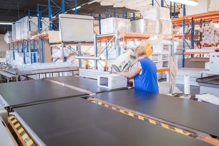 Industriële productie van matrassen. Fabrieksarbeider voltooit de productie van de matras monster