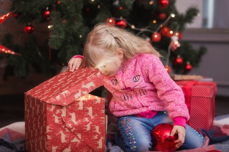 Adorable Little Girl Opening A Magical Christmas Gift By A Christmas ...