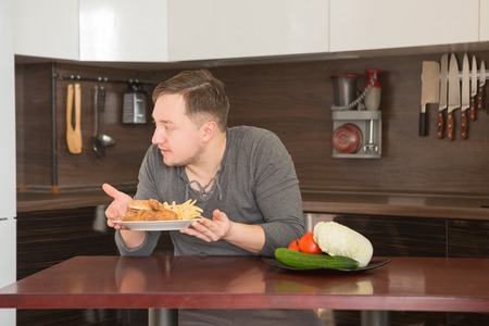wholesome: Man chooses between fast food and vegetables in the kitchen. Harmful - burger and fries unhealthy and wholesome food, lifestyle concept. Stock Photo