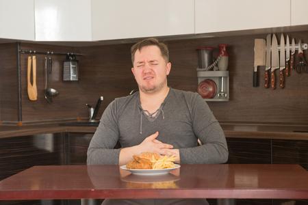 부엌에서 집에서 정크 푸드를 먹는 것을 거부 뚱뚱한 남자. 건강에 해로운 식품 개념입니다.