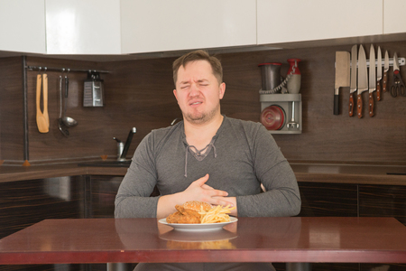 Fat man rejecting to eat junk food at home in the kitchen. Unhealthy food concept. Archivio Fotografico