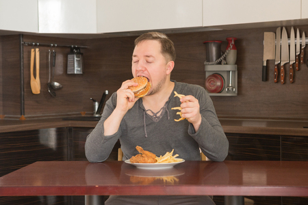 to restrain: Young man eat junk food at home in the kitchen with pleasure