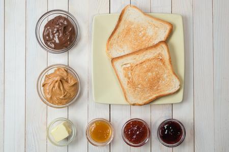 Sandwiches of toast met pindakaas, chocoladepasta en aardbei, bessen en abrikozengelei of jam op witte houten tafel, bovenaanzicht, plat leggen