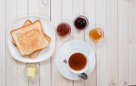 샌드위치 또는 딸기, 건포도와 살구 젤리 또는 흰색 나무 테이블, 평면보기, 평면 누워, 잼에 토스트와 홍차의 흰색 컵 복사 공간이있는 아침 개념 스톡 콘텐츠