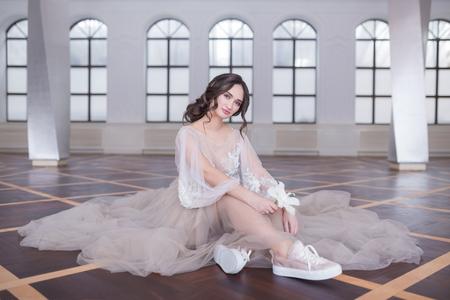아름 다운 행복 한 신부 웨딩 드레스와 스 니 커 즈 또는 바닥, 상위 뷰에 앉아 gumshoes의 높은보기 초상화