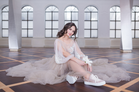 High view portrait of beautiful happy bride in wedding dress and Sneakers or gumshoes sitting on the floor, top view