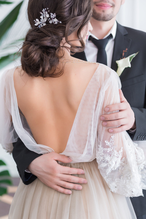 back alley: Beautiful brunette bride and groom portrait, back view, close up of gorgeous newlywed woman in stylish beige wedding dress with open back, rear view