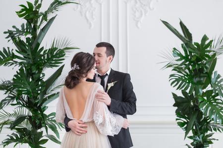 オープン バック、背面とスタイリッシュなベージュ結婚式ドレスの豪華な新婚女性の美しい背面図を新郎新婦ポートレートをブルネットをクローズ  写真素材