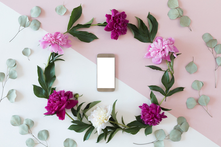 Flower arrangement on a white background with a mobile phone in a floral frame, top view and flat lay