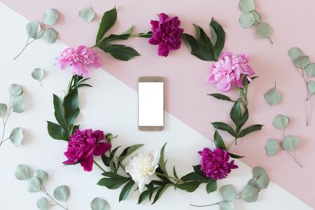 Het bloemstuk op een witte achtergrond met een mobiele telefoon in een bloemenkader, een hoogste mening en vlakte lag Stockfoto - 104289278