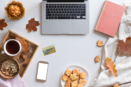 Top view of woman hands holding credit card on autumn baclground, business concept, online shopping, workspace with laptop, mobile phone, autumn leaves and flowers and notebook, cookies, flat lay. Stockfoto