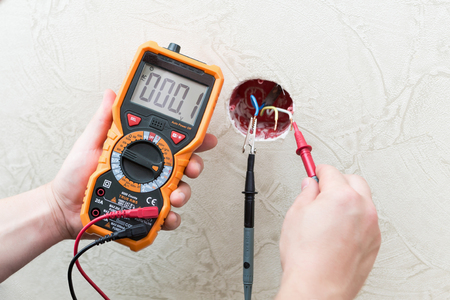 Close-up of man measuring and cheking power supply voltage with digital multimeter Фото со стока