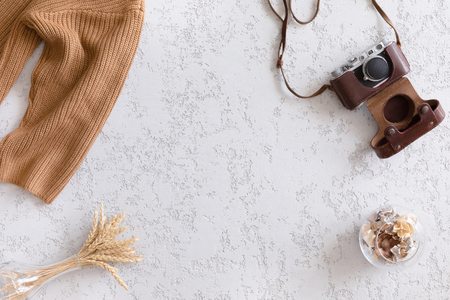 Hello Autumn flat lay background. Top view of workspace or office desk with vintage photo camera, sweater, autumn flowers and gold ears of wheat on textured white background Stock Photo