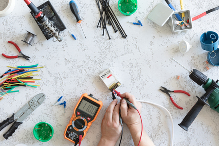 Top view of different electrical tools on white concrete background, flat lay. Tools for an electrician, measurement of voltage 110V and current measurements 스톡 콘텐츠