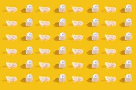 Top view of Rolls of toilet paper and White feather, seamless photographic pattern. Repetitive pattern with shadow on yellow background, flat lay.