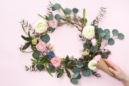 Festive flower wreath composition with kraft paper cornet and woman hand on pink background. Overhead view, flat lay