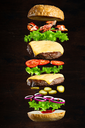 Floating burger isolated on black wooden background in men hands. Ingredients of a delicious burger with ground beef patty, lettuce, bacon, onions, tomatoes and cucumbers Stock fotó