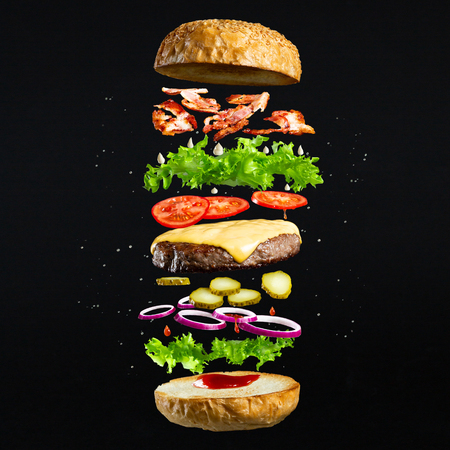 Floating burger isolated on black wooden background. Ingredients of a delicious burger with ground beef patty, lettuce, bacon, onions, tomatoes and cucumbers