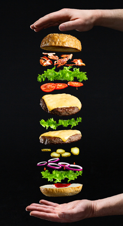 Floating burger isolated on black wooden background in men hands. Ingredients of a delicious burger with ground beef patty, lettuce, bacon, onions, tomatoes and cucumbers 스톡 콘텐츠