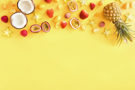 Exotic tropical fruits yellow background, banner or template. Colorful fresh exotic fruits on pastel yellow table. Pineapple, coconut, passion fruit, strawberry. Flat lay, top view, copy space