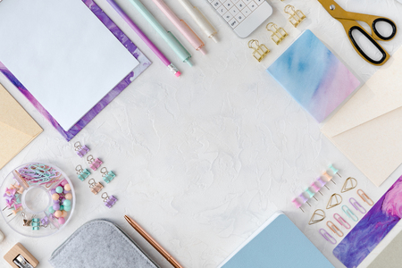 View from above of flatlay of stationery on white table background. Office or school stationery on pastel female desk 免版税图像