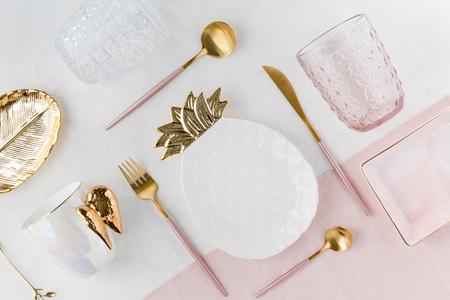 Flat lay of table decor. Top view of decorations for a serving festive table. White and golden pineapple plate, water glasses and pink cutlery on white background, flatlay.