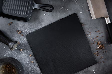 Black Slate board with Grill pan, knife with spices on a gray table, top view 스톡 콘텐츠