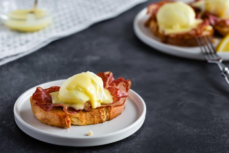 Bruschetta with parma ham and Egg Benedict. Classic Eggs Benedict with bacon, hollandaise sauce, English breakfast with tasty toasts