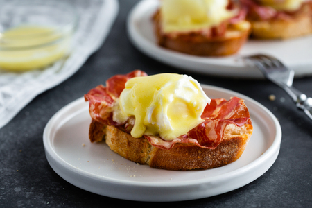 Eggs Benedict- toasted English bread, parm ham, poached eggs with hollandaise sauce and lemon on gray background